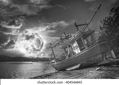 An old wooden fishing boat on a shingle beach under a full moon