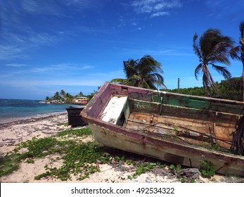 old wooden fishing boat rotting on beach with hotel in background North End Big Corn Island Nicaragua Central America