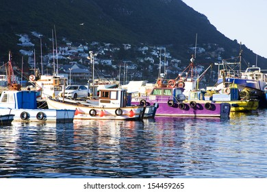 Old wooden fishing boats moored in Kalk Bay Harbour, Cape Town, South Africa