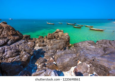 Old wooden fishing boats tied with a long rope to the shore in a colorful bright sea behind beautiful smooth stones on the shore of the Adaman Sea. Koh Lanta island coast, Krabi, Thailand.