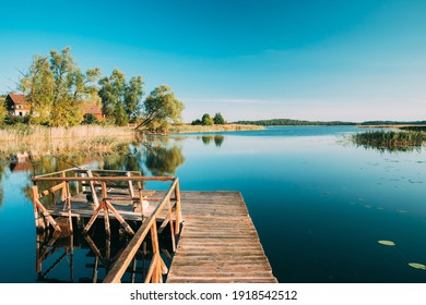 Old Wooden Fishing Pier Near Summer Lake Or River. Calm Water In Beautiful Summer Sunny Day