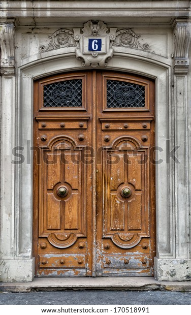 Old wooden front door in Paris. Aged and weathered with great character.