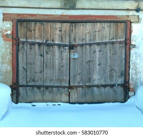 Old wooden garage doors covered with snow.