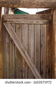 Old wooden gate leading to the courtyard. A stripped door in a country house. Closed vintage door with a gap.