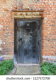 An old wooden gate in a red brick exterior garden wall in the UK