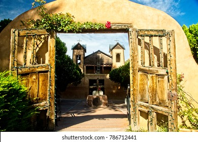 Old wooden gates in adobe wall at the entrance to the famous Chimayo Santuario chapel in New Mexico.