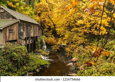 Old Wooden Grist Mill used for Grinding Flour and Grain in a Forest with Autumn Colored Trees Of Gold, Yellow and Orange Leaves along a Creek, Stream, with reflection and a Waterfall.