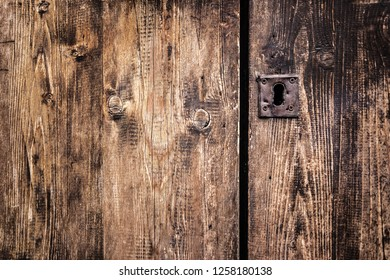 an old wooden and grungy locked door typical of the south of italy