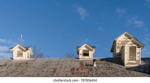 Old Wooden, Grungy, Peeling Paint Roof Dormers and Blue Sky