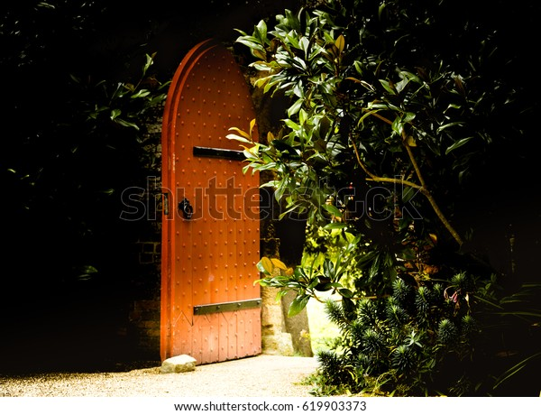 Old wooden heavy open door as entrance to the fairy tale. Garden at Arundel Castle in UK