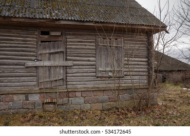 Old wooden house with door and window. Wall of an old house. An ancient building. Stone Foundation. Window and door boarded up. For design. Abandoned Collection
