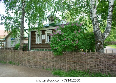 Old wooden house with a lilac Bush