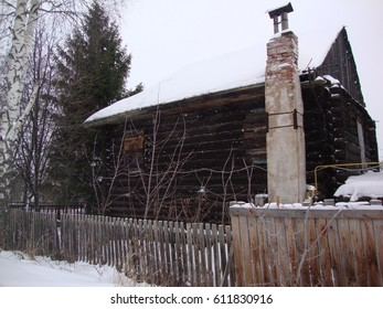 The old wooden house of logs with a remote oven