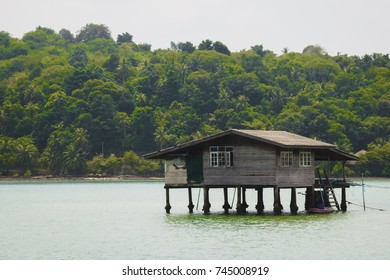 Old wooden house on the ocean in the fisherman village with green trees on the island and sky in the background. Koh Chang, Thailand.