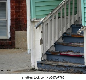 Old wooden house steps with blue peeling paint in urban neighborhood against a brick background