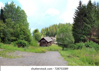 Old wooden hut on the slope near the lake and a forest
