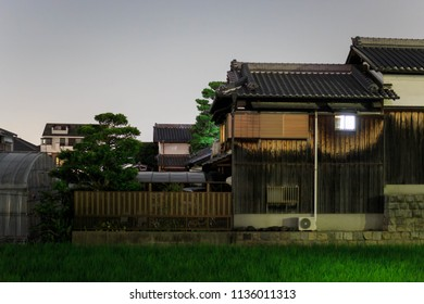 Old wooden Japanese home sits atop stone wall next to rice field at night