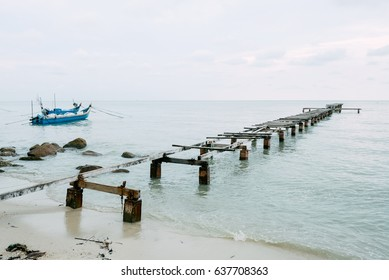 an old wooden jetty beyond the sea in a cloudy day