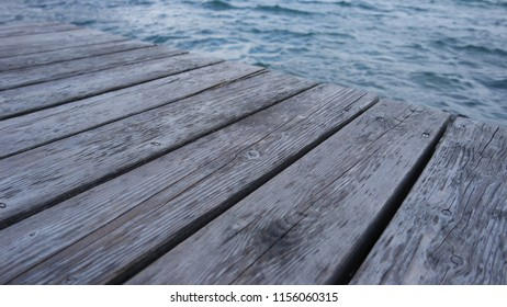 Old wooden jetty board floor and clear water, background, wooden texture.