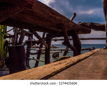 An old old wooden jetty bouncing on the beach.  The horizon is visible in the distance. Some stone in the sea.