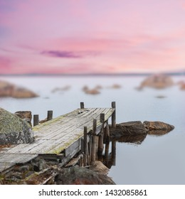 Old wooden jetty in calm lake at purple sunset