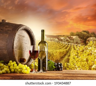 Old wooden keg with bottle and glass of red, white wine. Rural vineyard on background