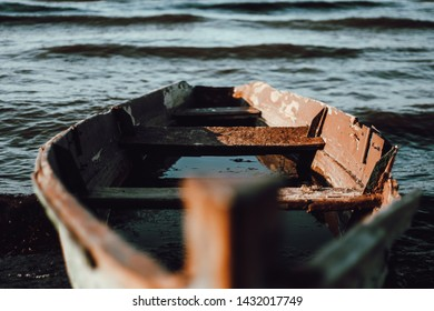 The old wooden leaky boat lieas on the shore of the lake