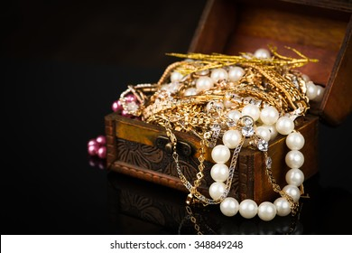 Old wooden open chest with golden jewelry on black background