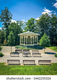 Old wooden ornamental gazebo with lonely man enjoying tranquil atmosphere