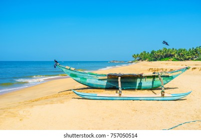 Old wooden oruwa boat of the local fishermen on the scenic sand beach on Bentota, Sri Lanka.