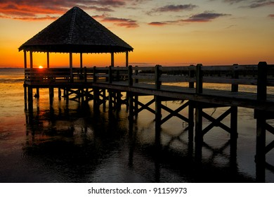 Old wooden pavilion on the shore at sunset