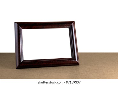 Old wooden photo frame on table isolated on white background