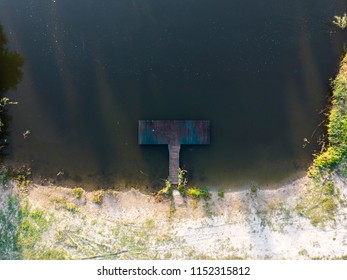 Old wooden pier in calm river from above in the morning. Susrise in nature.