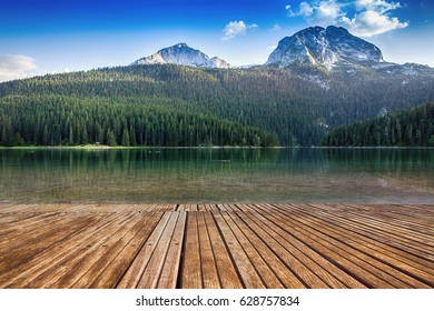 Old wooden pier with crystal clear lake. Montenegro, national park Durmitor, mountains and clouds. Nature travel background