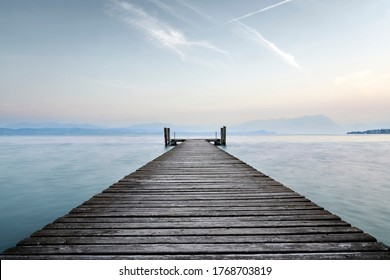 An old wooden pier extends into the clear blue waters of the lake. A solitary path towards the calm and peaceful silence of nature, with the sweet sound of the waves.