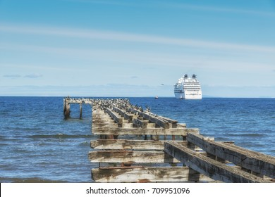 Old wooden pier in Punta Arenas with cruise ship on the background. The Strait of Magellan. Chilean Patagonia