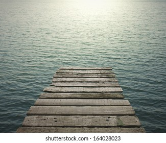 Old wooden pier to the sea with sunlight reflection, background