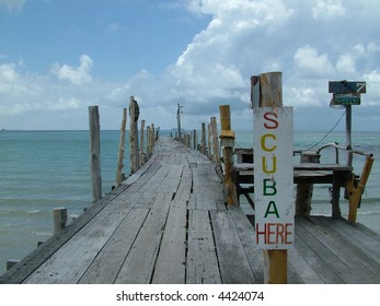 An old wooden pier with a sign advertising scuba rental