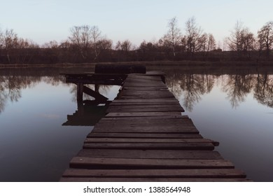 old wooden pier at small beautiful pond on sunset vertical