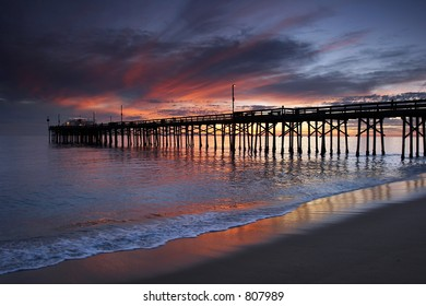 Old wooden pier at sunset with some people walking and fishing.