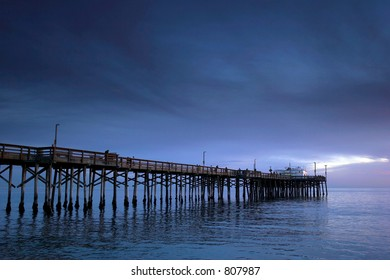 Old wooden pier with surrounded by blue water and blue clouds. There are some people walking and fishing.