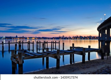 Old wooden piers stand empty in the still waters of the Severn River at twilight. Colorful skies on the horizon at dusk, along with the evening lights of the Naval Academy and Annapolis, Maryland.