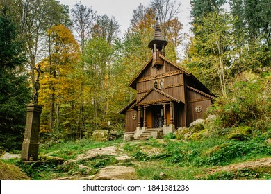 Old wooden pilgrimage rural Chapel of Virgin Mary (CZ: Stozecka kaple) and iron cross, standing in a forest at the altitude of 950 m, Czech Republic, Sumava National Park. Folk wood carving.