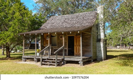 An old wooden pioneer home, circa early 1900s, with a rocking chair on the front porch. Wooden shakes are on the roof and there is a white brick chimney. Tall oak tree behind, and more trees on sides.