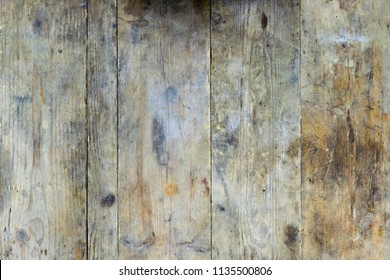 Old wooden planks from a workbench that are dirty and soiled with oil and rust