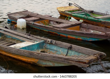 Old wooden punt boats. Three vintage wooden boats with old colors. Photo of three old fishing wherry tied to the shore. Three old punt boats or rowing boats.
