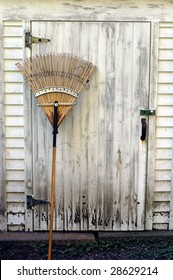 An old wooden rake leans against a dirty work shed.