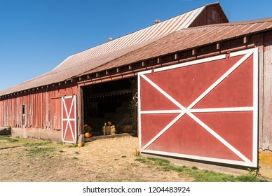 Old Wooden Red Barn on Rural Farm, Metal Roof and Red and White Barn Door