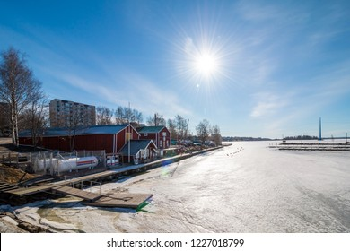 Old wooden red houses on the riverside. City architecture of Vaasa in background. Finland