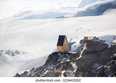 Old wooden restroom for climbers about break on edge of the cliff on permafrost glaciers on Elbrus mountain